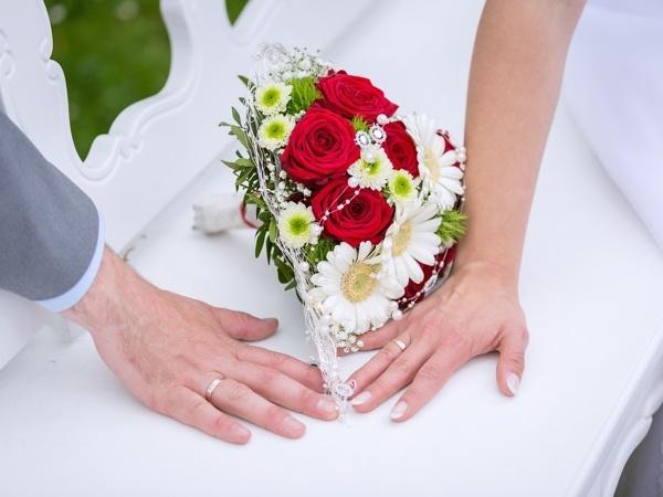 zwei Hände mit Blumenstrauß