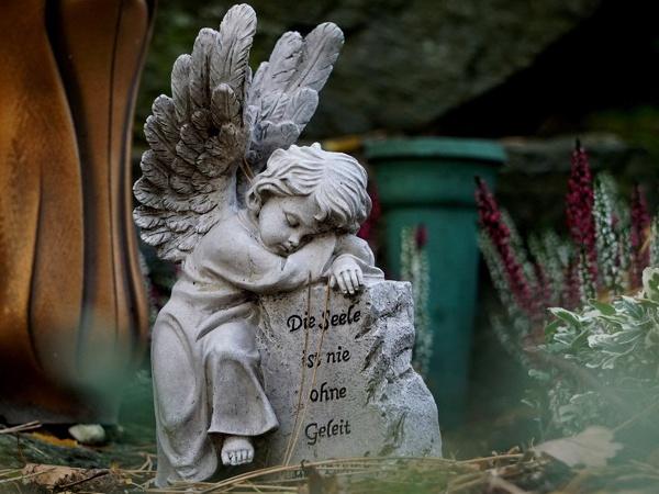 Figur schlafender Engel auf einem Stein